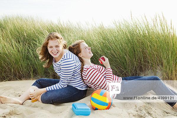 Teenager lachend in Dünen sitzend