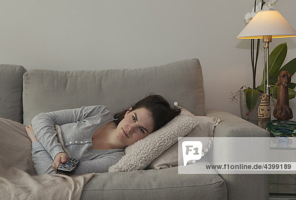 Junge Frau mit TV-Fernbedienung
