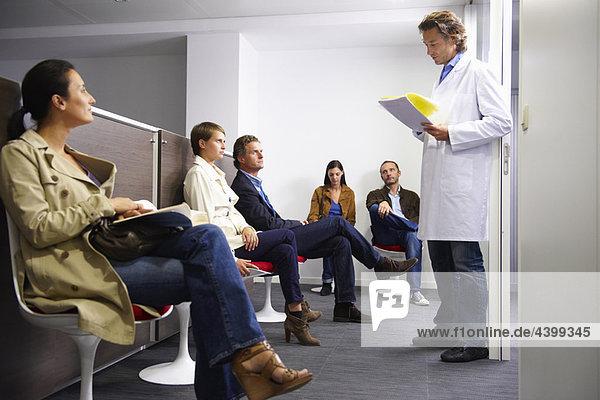 Arzt ruft einen Patienten im Wartezimmer an
