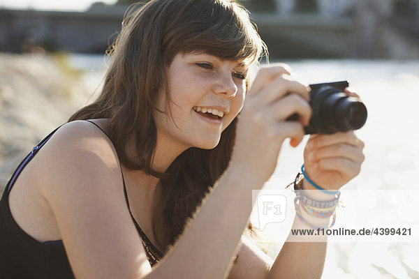Young girl taking a picture and laughing