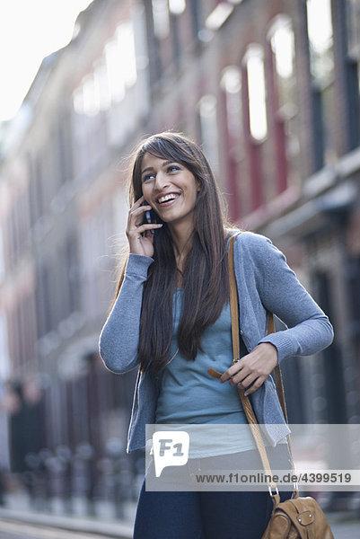 Junge Frau am Telefon in der Straße