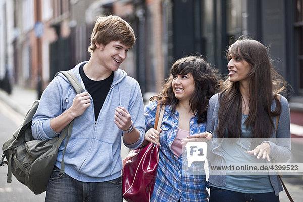 3 junge Leute  die auf der Straße gehen