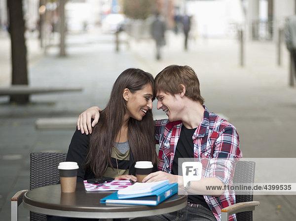 Paar am Kaffeetisch sitzend  umarmend