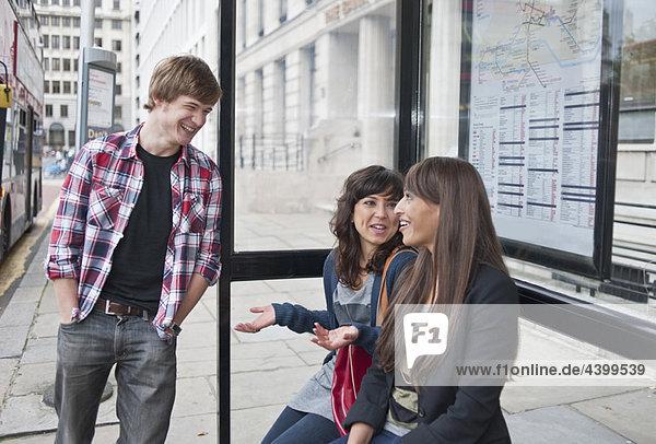 Freunde warten an der Bushaltestelle
