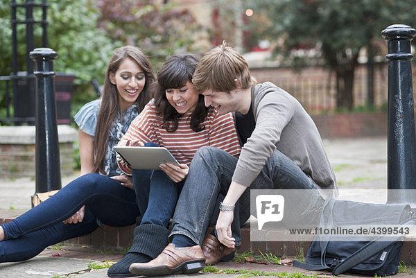 Freunde teilen Laptop draußen