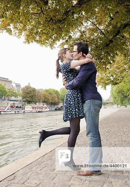 Romantisches Ehepaar küsst sich an der Seine