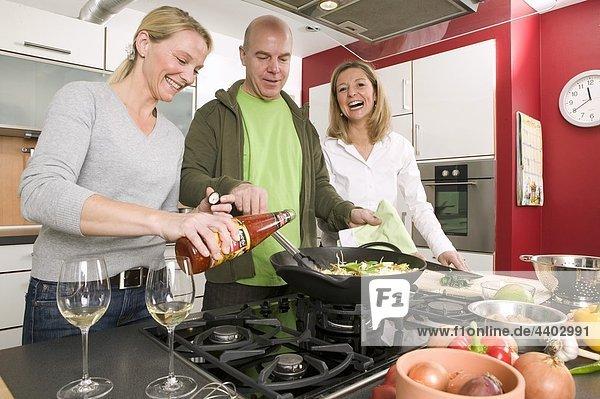 Mann und zwei Frauen kochen ein rühren-braten zusammen