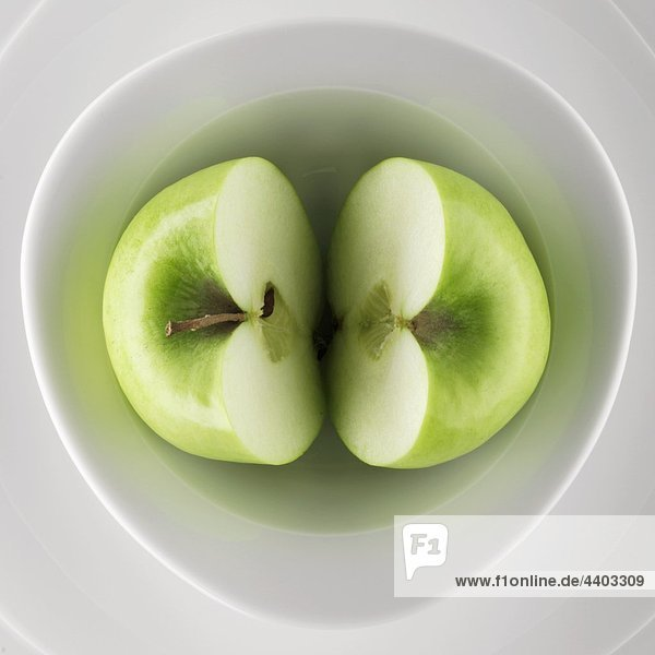 Halbierte grüner Apfel in eine Schüssel geben