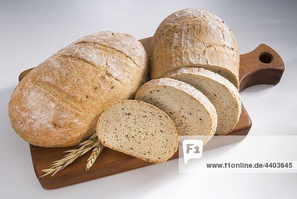 Vollständige und teilweise geschnittene Laibe Brot auf einem Holzbrett