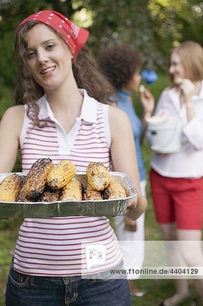Junge Frau mit Gegrillter Mais Maiskolben bei einem barbecue