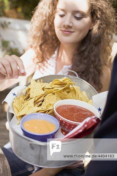 Frau erreichen für Tortilla Chips mit zwei Absinken der Schüssel