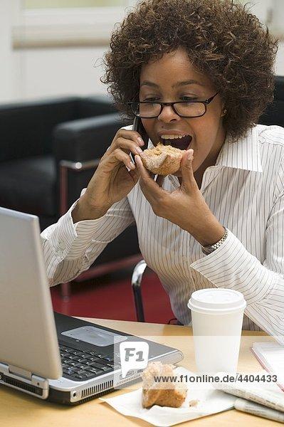 Frau isst Muffin während der Arbeit am computer
