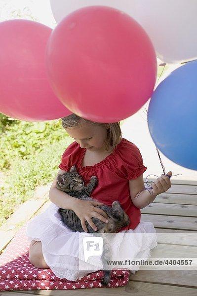 Kleines Mädchen halten Katze und Ballons (4. Juli  USA)