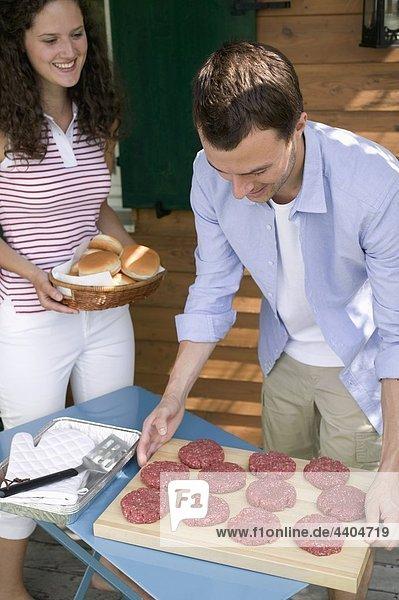 Mann zum Grillen  Frau bringen Brötchen Burger vorbereiten