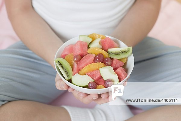 Seated woman holding dish of fruit salad