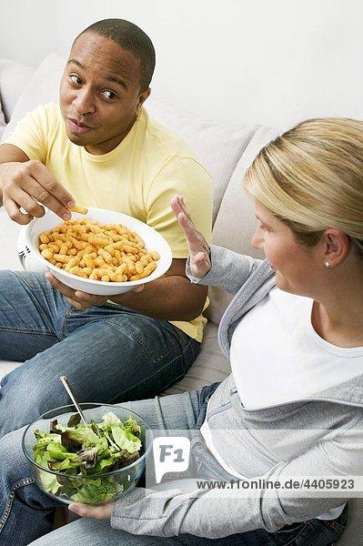 Paar auf Sofa mit Erdnuss Puffs und Salat