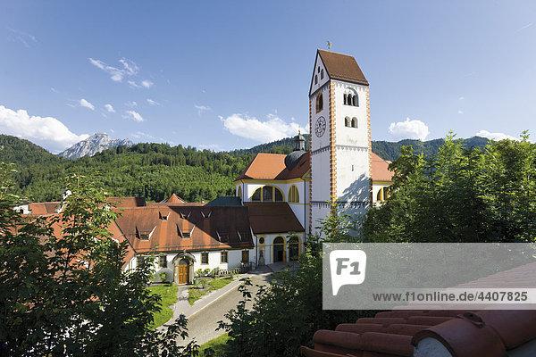 Deutschland  Bayern  Allgäu  Füssen  Blick auf die St.-Magnus-Kirche mit Bergen im Hintergrund