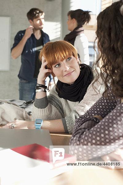 Frauen im Gespräch mit Studenten im Hintergrund