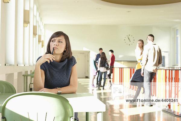 Frau sitzend im Flur  Schüler stehend im Hintergrund