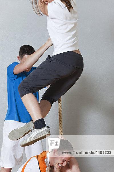 Junge Männer und Frauen  die in der Turnhalle klettern.