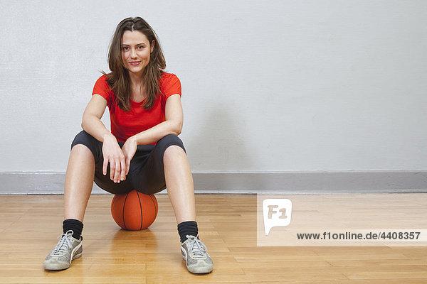 Junge Frau sitzt auf Basketball in der Turnhalle und lächelt.