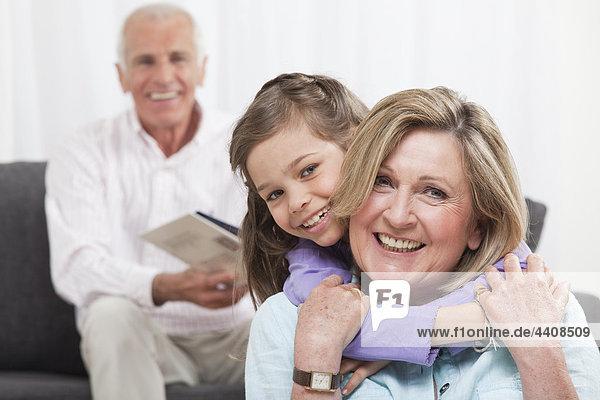 Enkelin (6-7) umarmt Großmutter mit Großvater im Hintergrund