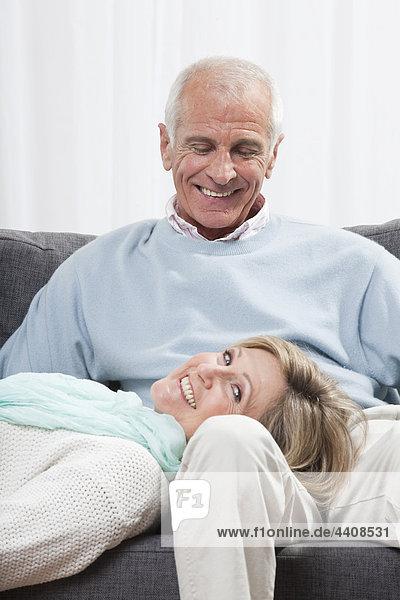 Mann sitzend mit Frau auf dem Schoß liegend  lächelnd