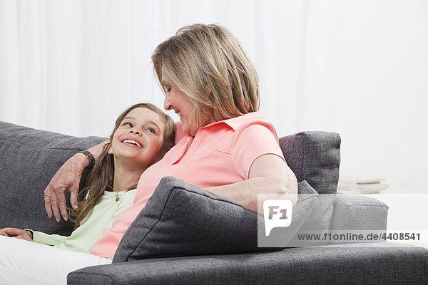 Enkelin (6-7) und Großmutter auf der Couch sitzend  lächelnd