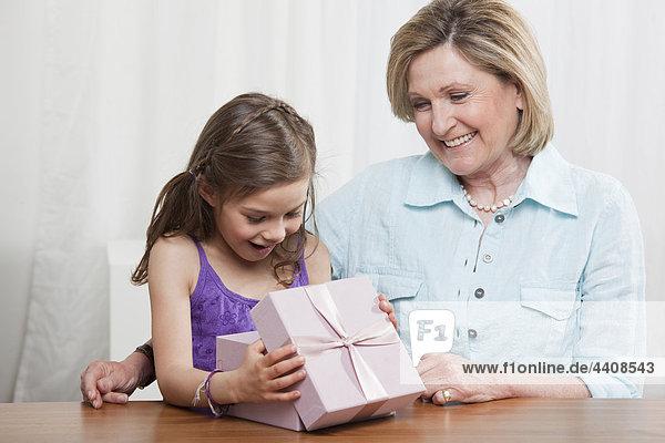 Enkelin (6-7) öffnet Geschenkbox und Großmutter lächelt
