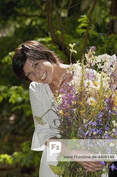 Österreich  Salzburger Land  Frau mit Wildblumenstrauß  lächelnd  Nahaufnahme