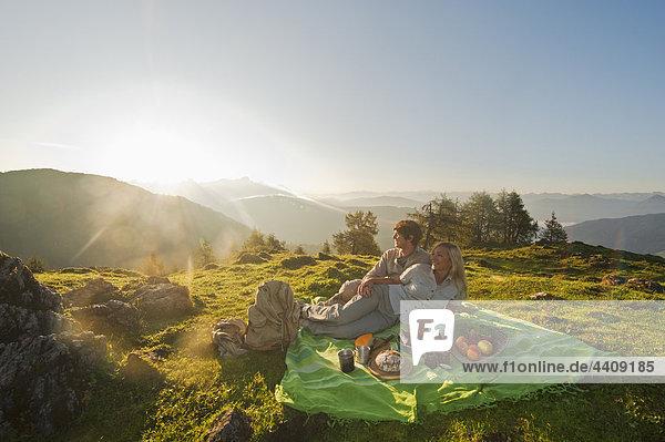 Junges Paar auf der Decke liegend  mit Blick auf die Aussicht.