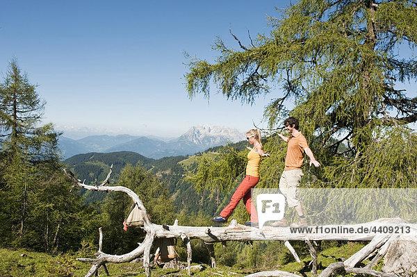 Junges Paar balanciert auf umgestürztem Baumstamm.
