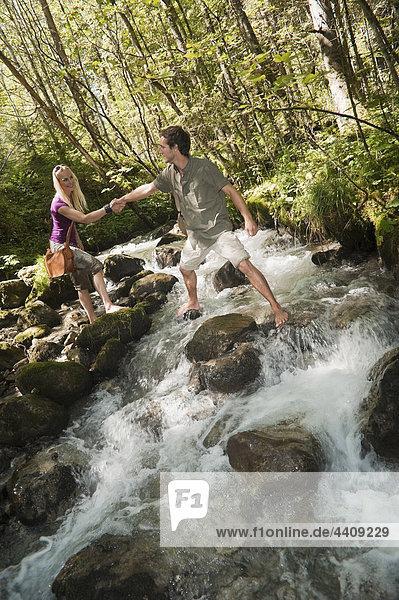 Österreich  Steiermark  Mann hilft Frau beim Überqueren des Flusses  Händchen haltend