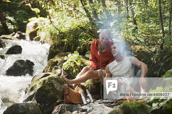 Österreich  Steiermark  Junges Paar sitzt am Lagerfeuer am Bach im Wald
