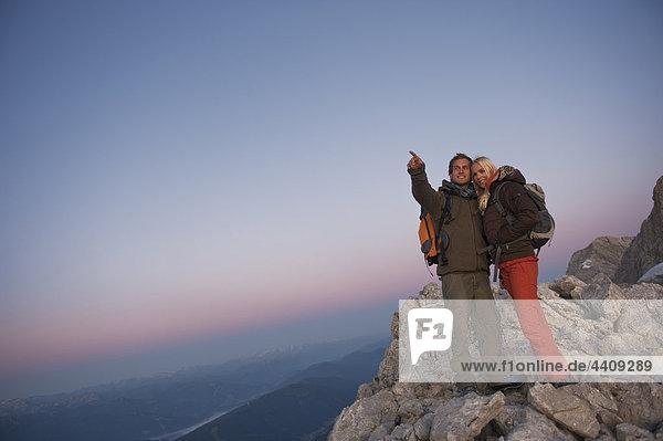 Österreich  Steiermark  Dachstein  Paar auf Berggipfel  Mann zeigt weg