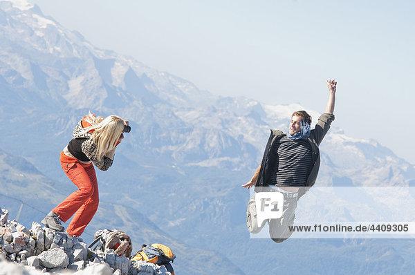 Österreich  Steiermark  Dachstein  Frau beim Fotografieren  Mann beim Springen