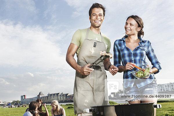 Mann und Frau beim Grillen mit Freunden im Hintergrund