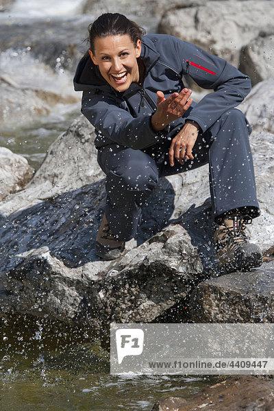 Italien  Trentino  Junge Frau spielt mit Flusswasser