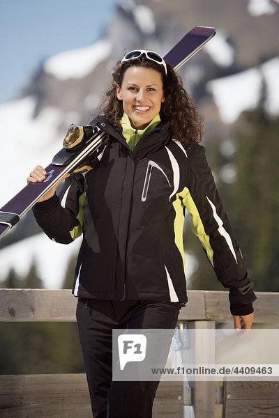 Italien  Südtirol  Frau mit Skiern  lächelnd  Portrait