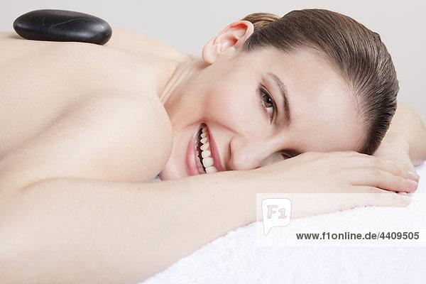 Frau mit einer Hot-Stone-Behandlung  lächelnd  Portrait