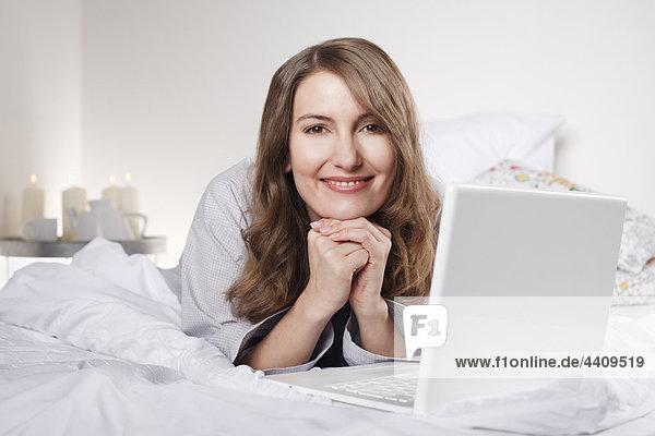 Frau auf dem Bett liegend mit Laptop  lächelnd  Portrait