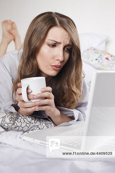 Frau auf dem Bett liegend mit Kaffeetasse und Laptop