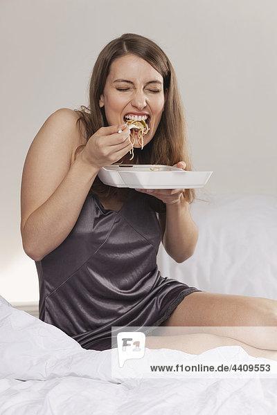 Frau  die auf dem Bett sitzt und asiatisches Essen isst.
