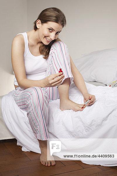 Frau sitzt auf dem Bett und trägt Nagellack auf