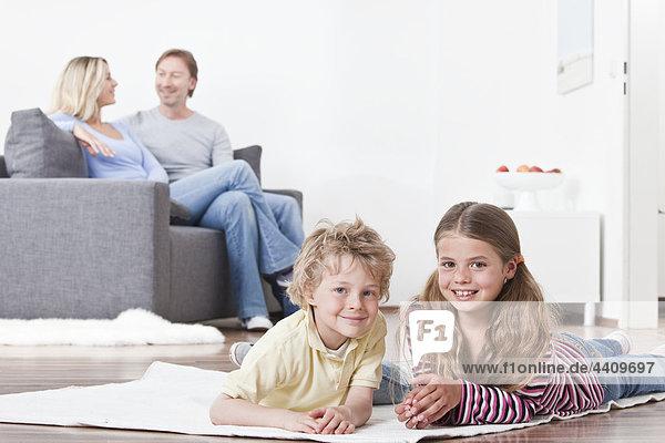 Kinder lächeln mit Eltern im Hintergrund