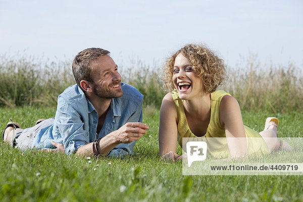 Man and woman lying on grass  smiling