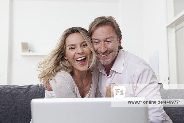 Paar mit Laptop  lächelnd