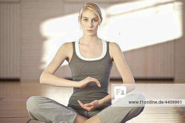 Frau sitzend in Yoga-Pose auf Übungsmatte  Portrait