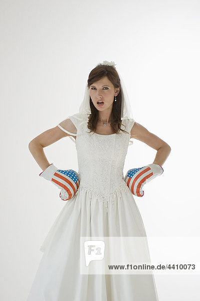 Braut trägt Boxhandschuhe mit Hand auf HüfteBride trägt Boxhandschuhe mit Hand auf Hüfte