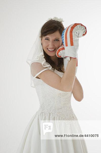 Porträt einer Braut mit Boxhandschuhen  lächelnd